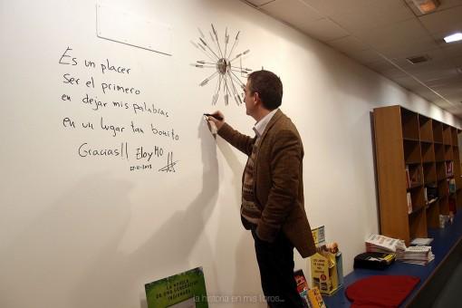 Santiago firmando en la pared de autores de Librería Birdy